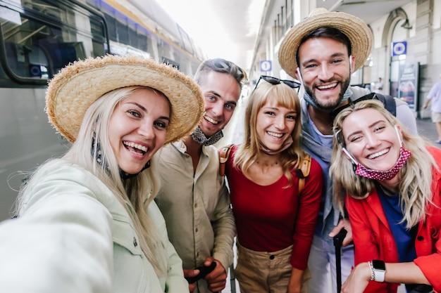 Multiraciale groep vrienden die een gezichtsmasker dragen en een selfie nemen op het treinstation. reizen, vakantie en vakantie nieuw normaal concept