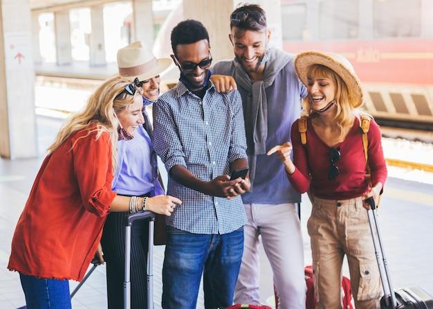 Multiraciale groep vrienden die gezichtsmasker dragen die smartphone gebruiken bij treinstation