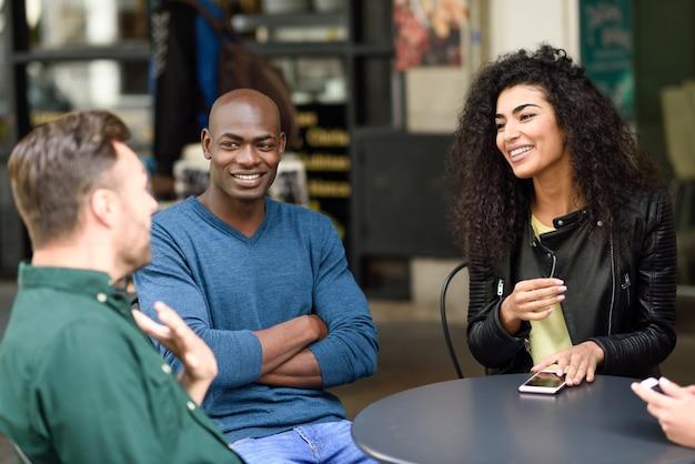 Multiraciale groep vrienden die samen een koffie wachten