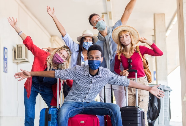 Multiraciale groep vrienden op treinstation met bagage die beschermend masker draagt.