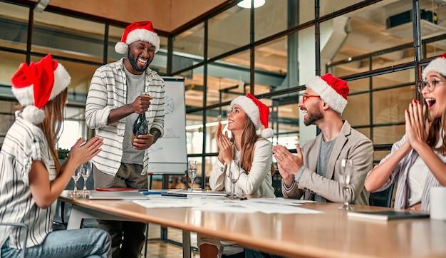 Multiraciale jonge creatieve mensen vieren vakantie in een modern kantoor.