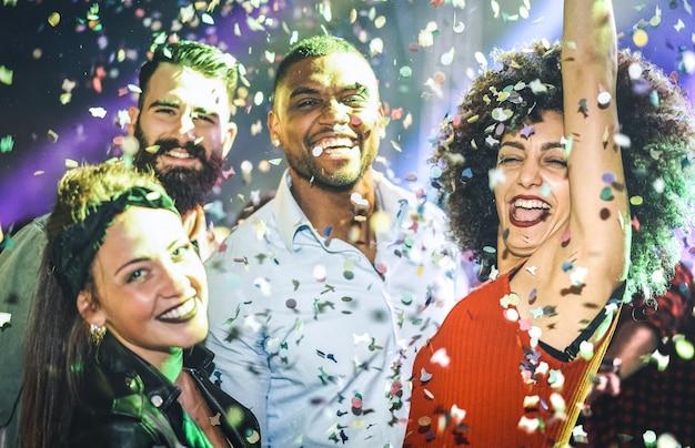 Multiraciale jonge vrienden die bij nachtclub onder confettienregen dansen