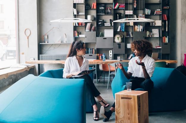 Multiraciale jonge vrouwen die voor nieuw project in modern bureau werken