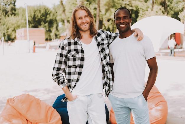 Multiraciale jongens op strandjongens knuffelen en nemen foto