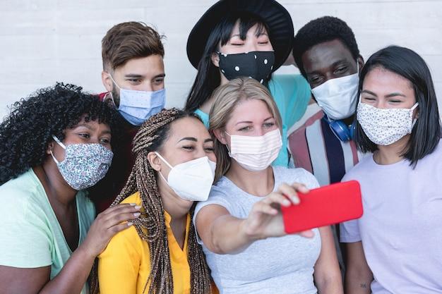 Multiraciale jongeren die selfie met telefooncamera nemen terwijl ze beschermende maskers dragen