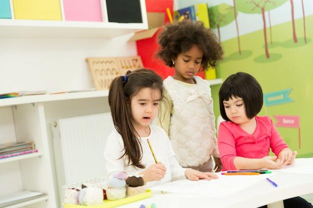 Multiraciale kinderen tekenen in de speelkamer