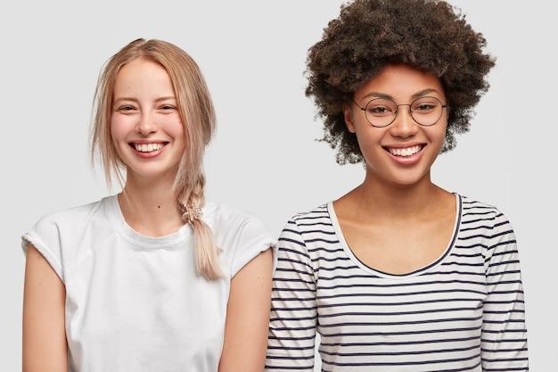 Multiraciale lesbische koppels hebben positieve uitdrukkingen. de gelukkige jonge blonde europese vrouw en haar beste afro-amerikaanse vriend glimlachen breed, in hoge geest. emoties en vriendschapsconcept