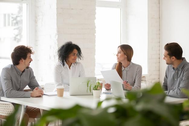 Multiraciale mannelijke en vrouwelijke collega's die bespreking hebben bij teamvergadering
