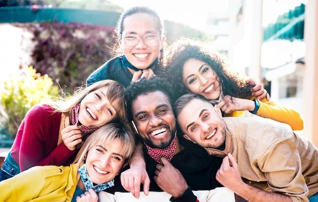 Multiraciale mensen die buiten selfie met geopend gezichtsmasker nemen