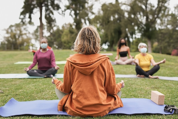 Multiraciale mensen die een veiligheidsmasker dragen voor een uitbraak van het coronavirus terwijl ze yoga-meditatie doen in het stadspark