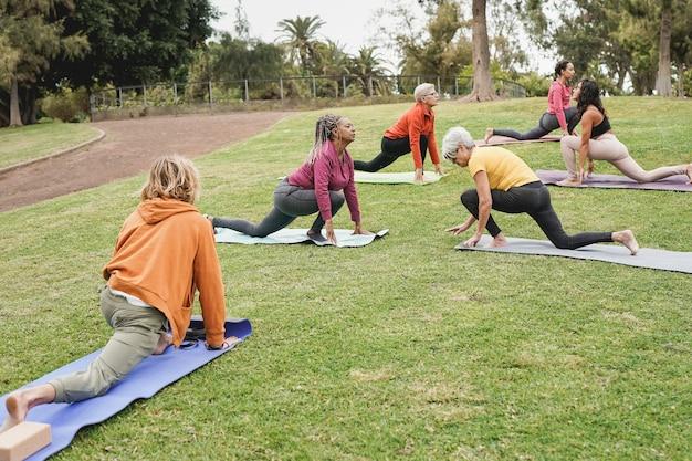 Multiraciale mensen die yoga doen in het park - concept van een gezonde levensstijl, sport en mensen van meerdere generaties