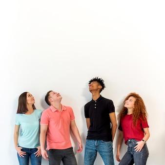 Multiraciale mensen die zich op een rij tegen het witte oppervlak opstaan
