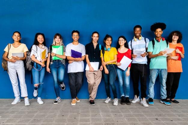 Multiraciale middelbare scholieren kijken naar camera op blauwe achtergrond terug naar school onderwijs