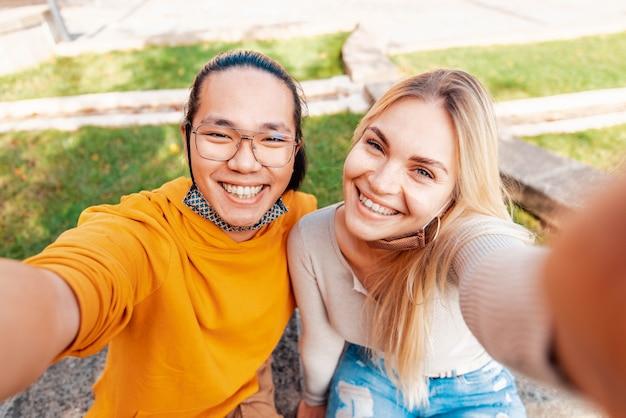 Multiraciale paar dragen van beschermend gezichtsmasker nemen een selfie buiten