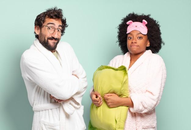 Multiraciale paar vrienden die hun schouders ophalen, zich verward en onzeker voelen, twijfelen met gekruiste armen en een verbaasde blik.