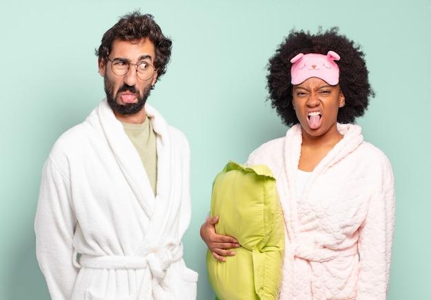 Multiraciale paar vrienden die walgen en geïrriteerd zijn, hun tong uitsteken en een hekel hebben aan iets smerigs en vies. pyjama's en huisconcept