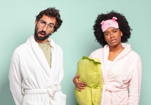 Multiraciale paar vrienden die zich verbaasd en verward voelen, met een domme, verbijsterde uitdrukking op zoek naar iets onverwachts. pyjama's en huisconcept