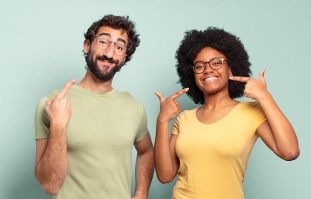Multiraciale paar vrienden glimlachend vol vertrouwen wijzend op hun eigen brede glimlach, positieve, ontspannen, tevreden houding