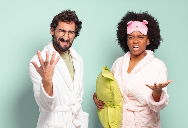 Multiraciale paar vrienden kijken boos, geïrriteerd en gefrustreerd schreeuwend wtf