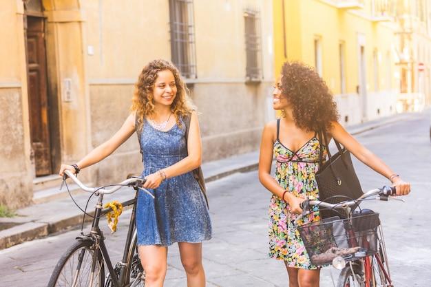 Multiraciale paar vrienden met fietsen in de stad