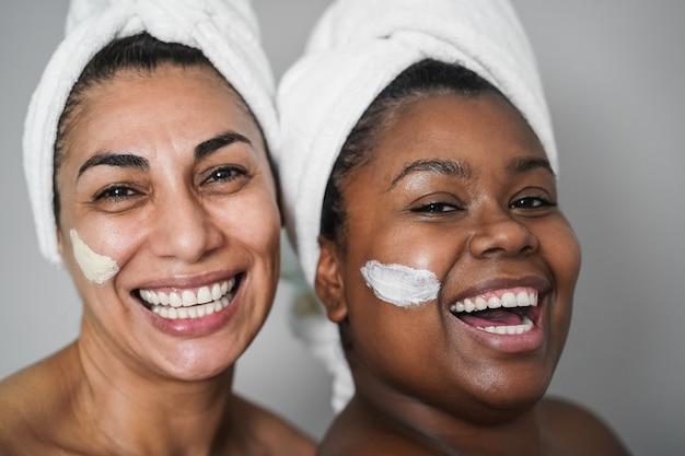 Multiraciale senior en jonge vrouwen die schoonheidsbehandelingen doen met huidmaskers - lichaamsverzorgingsconcept - focus op het oog van de afrikaanse vrouw