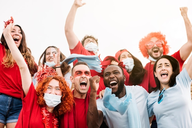 Multiraciale supporters die een beschermend gezichtsmasker dragen terwijl ze hun team steunen