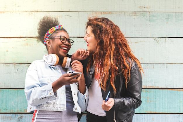 Multiraciale tiener meisjes met mobiele telefoon buitenshuis.