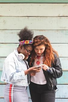 Multiraciale tiener meisjes met mobiele telefoon buitenshuis