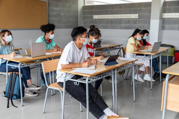 Multiraciale tiener middelbare scholieren in de klas dragen beschermende gezichtsmaskers onderwijs gezondheidszorg