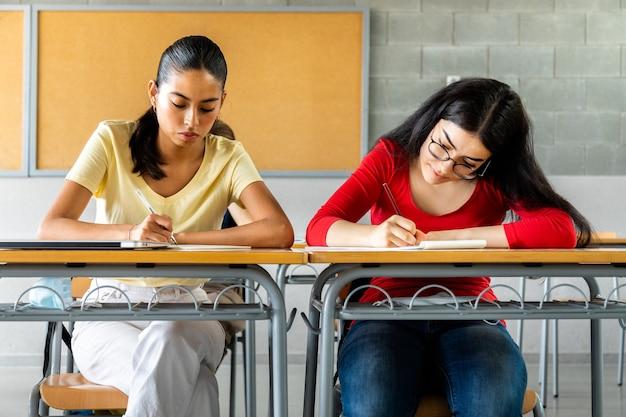 Multiraciale tiener middelbare schoolmeisjes doen huiswerk in de klas. onderwijsconcept.