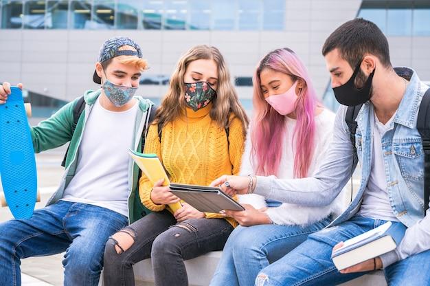 Multiraciale tienervrienden dragen gezichtsmasker zittend op de bank buiten de school - nieuw normaal levensstijlconcept met jonge studenten die samen studeren in de buurt van de campus buiten