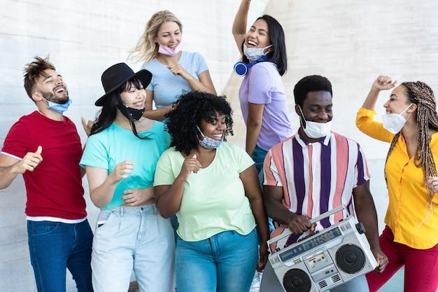 Multiraciale vrienden dansen op muziek met boombox stereo buiten met maskers onder de kin