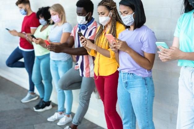 Multiraciale vrienden die beschermende gezichtsmaskers dragen tijdens het gebruik van de mobiele telefoon buitenshuis