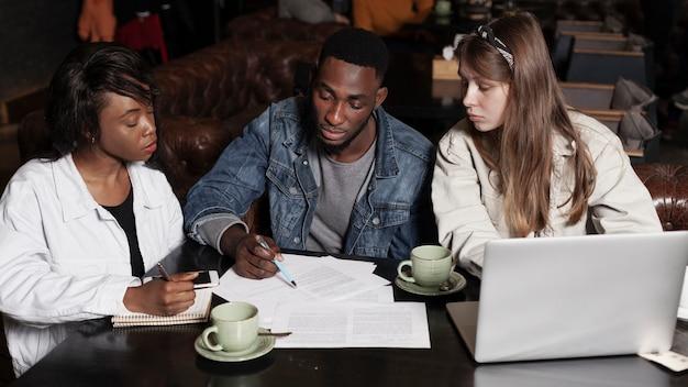 Multiraciale vrienden die binnenshuis werken