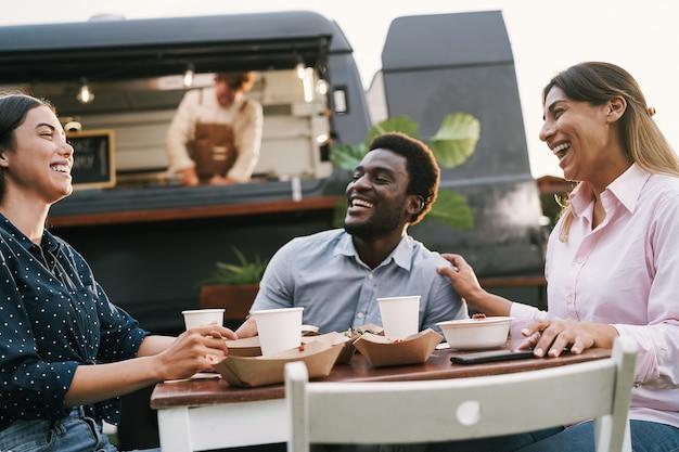Multiraciale vrienden die buiten aan de tafel van een foodtruck eten - zomer- en levensstijlconcept - hoofdfocus op het juiste gezicht van de vrouw
