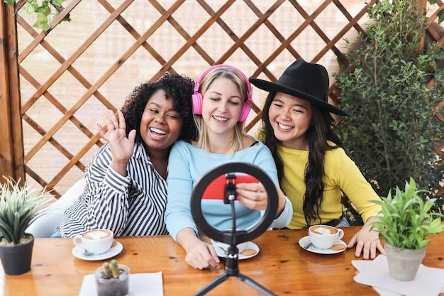 Multiraciale vrienden die online met de camera van de mobiele telefoon buiten bij restaurant streamen
