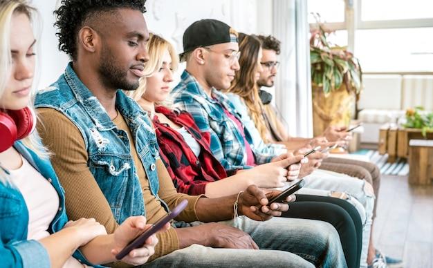 Multiraciale vrienden groeperen zich op verveeld moment met behulp van mobiele slimme telefoon - selectieve aandacht