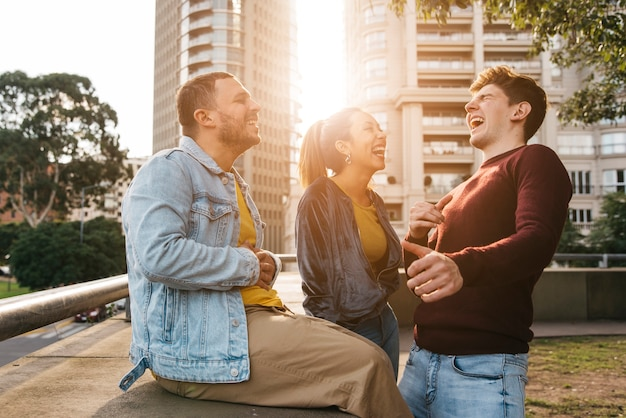 Multiraciale vrienden lachen bij zonsondergang