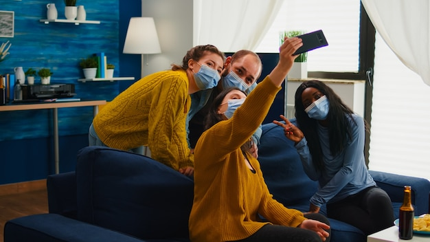 Multiraciale vrienden nemen selfie met gezichtsmaskers tijdens covid 19-uitbraak, nieuw normaal levensstijlconcept met mensen die plezier hebben in de woonkamer met respect voor sociale afstand om verspreiding van virussen te voorkomen