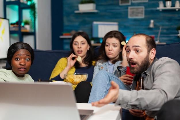 Multiraciale vrienden ontspannen op de bank terwijl ze kijken naar komedie die er tijdens de filmavond geschokt uitziet. groep multi-etnische mensen die samen tijd doorbrengen met bier drinken en 's avonds laat snacks eten.