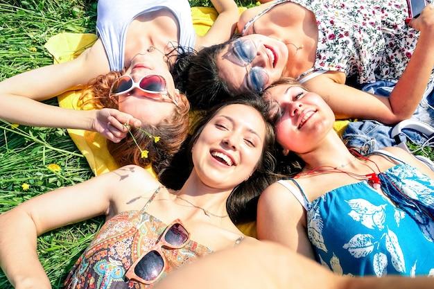 Multiraciale vriendinnen selfie te nemen op plattelandspicknick - gelukkig vriendschapsconcept en plezier met jongeren en nieuwe technologietrend - zonnige middagkleuren - ingelijst hand met smartphone