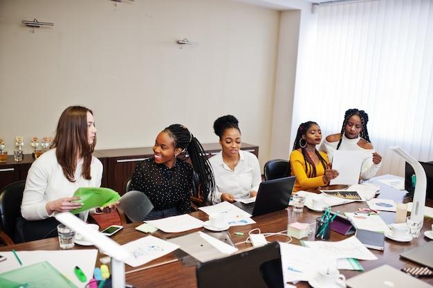 Multiraciale vrouwelijke collega's, bemanning van divercity vrouwelijke partners in het kantoor zitten aan de tafel.