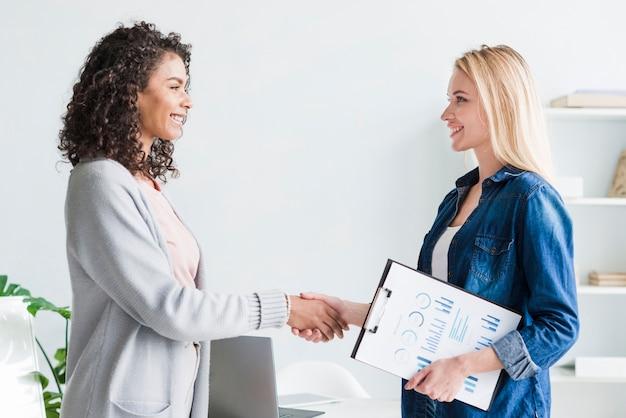 Multiraciale vrouwelijke werknemers die handen op kantoor schudden