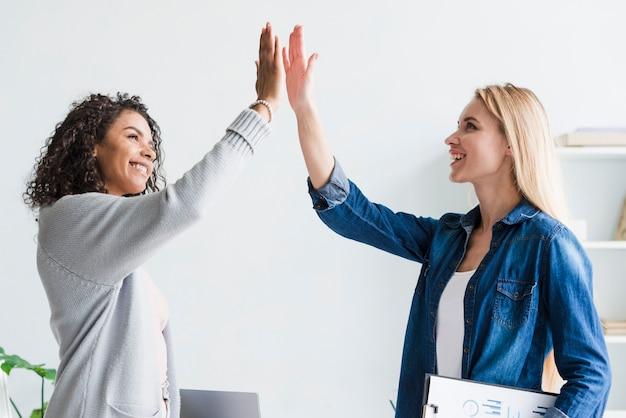 Multiraciale werknemers geven high five op kantoor