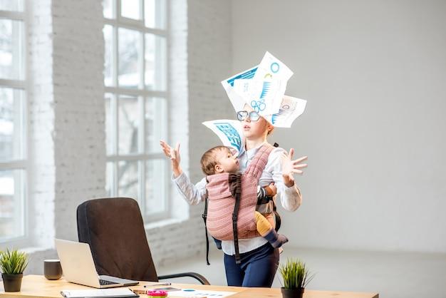 Multitasking en uitgeputte zakenvrouw die documenten overgeeft die bij haar zoontje staan tijdens het werk op kantoor
