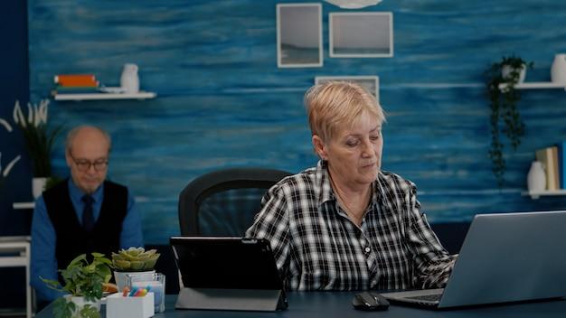 Multitasking gepensioneerde vrouw die tegelijkertijd op laptop en tablet leest