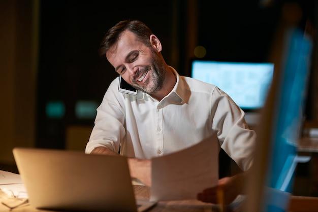 Multitasking man die laat op kantoor werkt