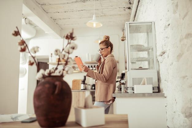 Multitasking. slimme zakenvrouw die koffie drinkt en berichten leest op haar oranje tablet.