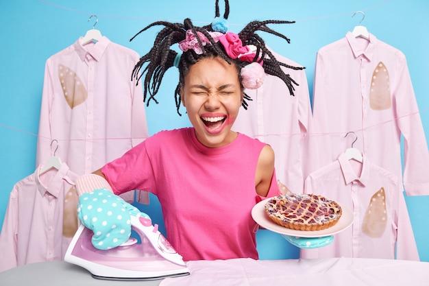 Multitasking vrolijke etnische vrouw strijkt kleding