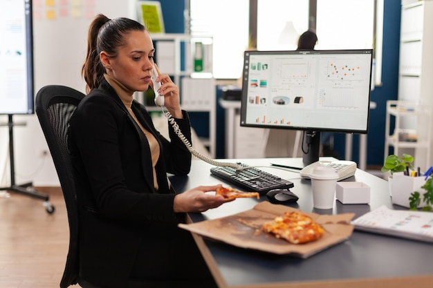 Multitasking zakenvrouw die aan de vaste lijn praat en bedrijfsgrafieken uitlegt aan een externe collega terwijl ze afhaalmaaltijden bestelt aan de balie. manager die proeverij pizzapunt eet?
